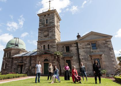 People standing on lawn in front of Sydney Observatory
