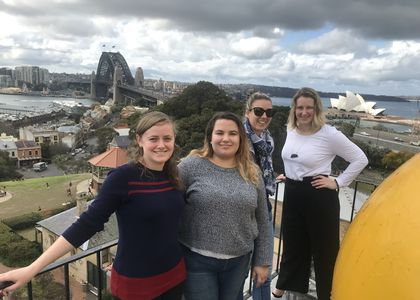 Four women pose for a photo with The Sydney Harbour Bridge and The Opera House in the background.