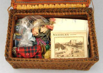 Open sewing box made of wicker with soft lining filled with a collection of sewing materials
