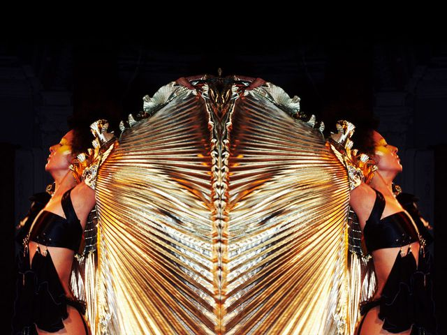 Two people with gold dresses on a black background.