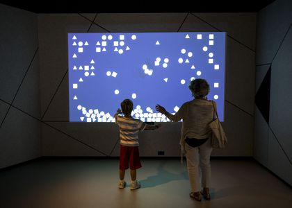 Woman and boy using arm movements to interact with the game being projected onto the wall before them