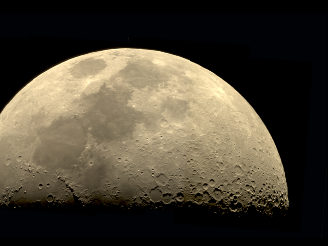 Close up photo of the first quarter moon, tinged yellow