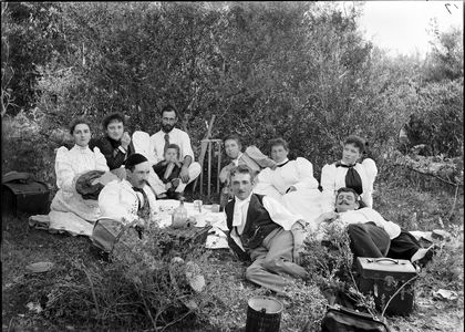 Black and white photo of a group of adults on a picnic in 1895
